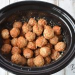 Pouring broth over meatballs in crockpot