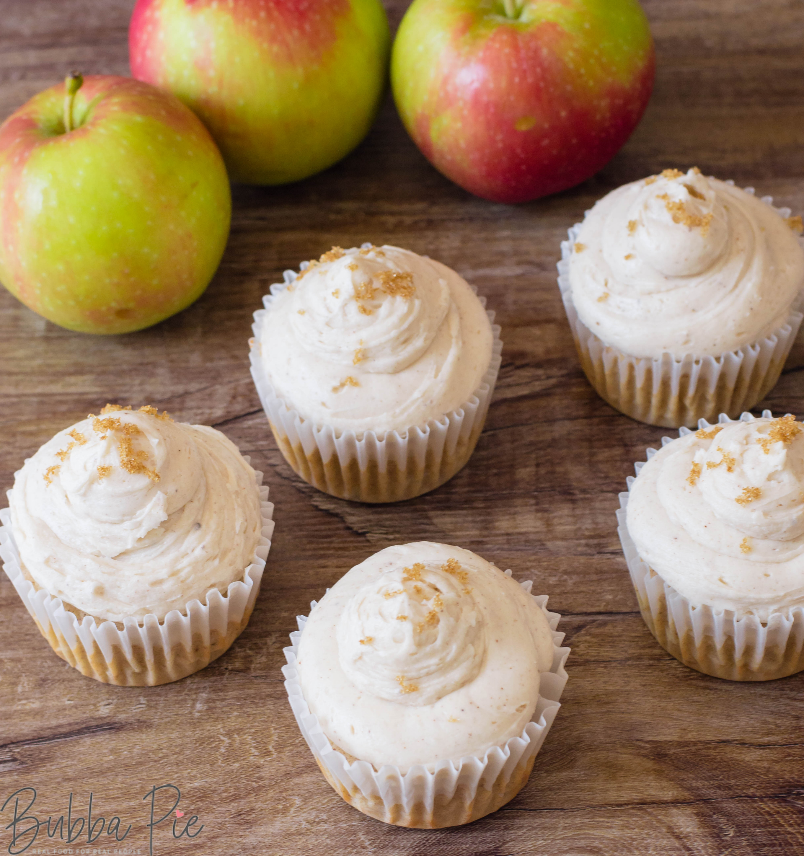 Apple Cinnamon Cupcakes sitting on a table with holiday decorations