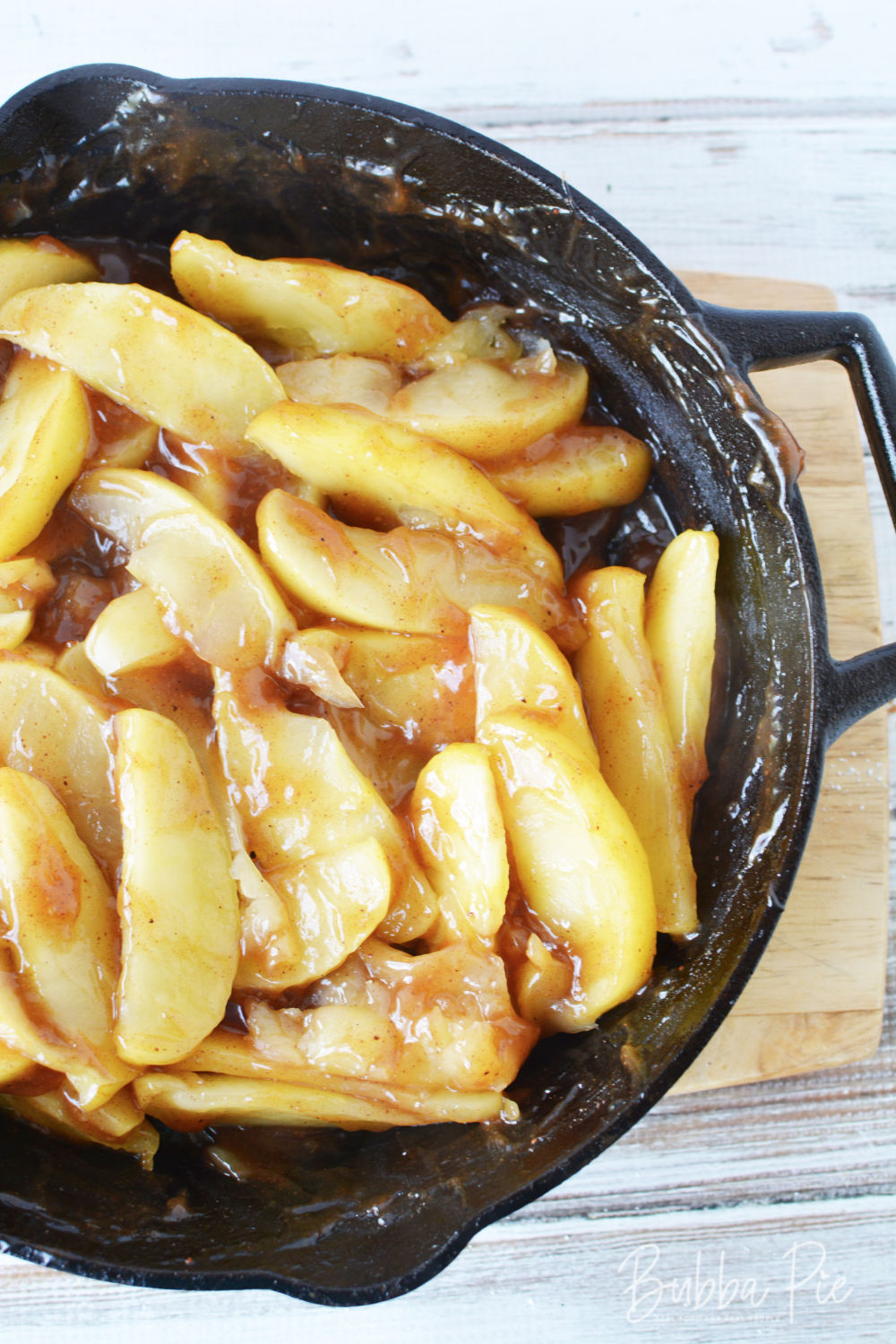 cracker barrel fried apples sitting in a skillet on a cuttingboard