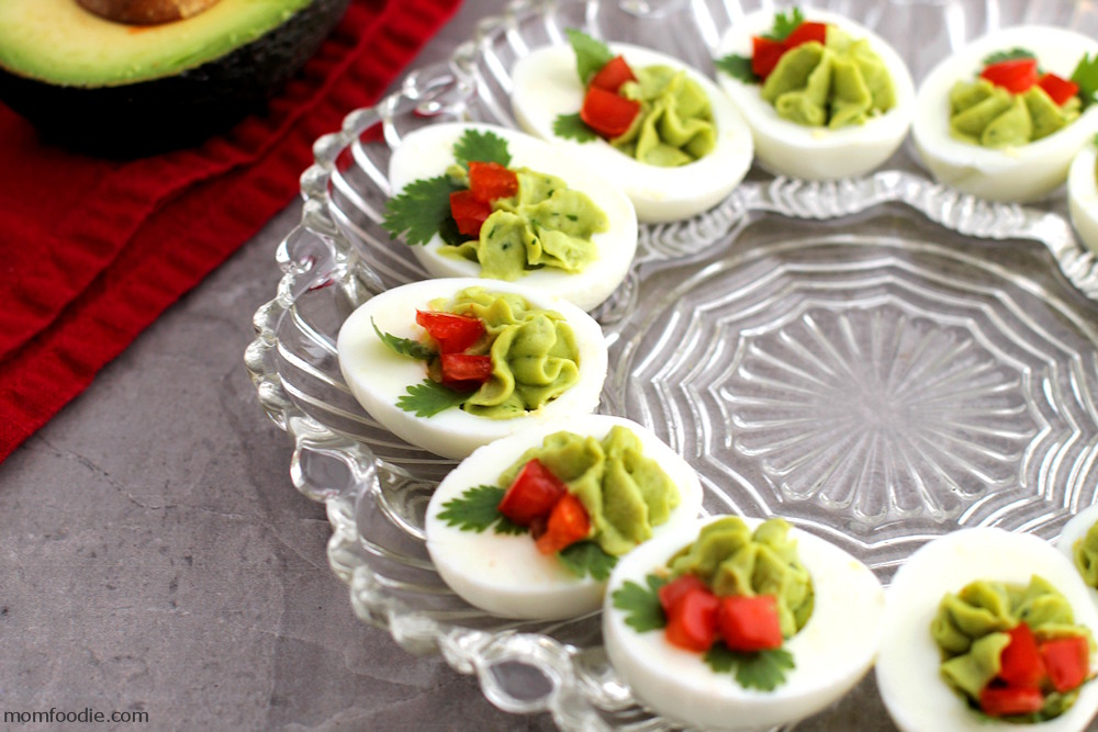 Christmas Deviled Eggs being served on glass tray.