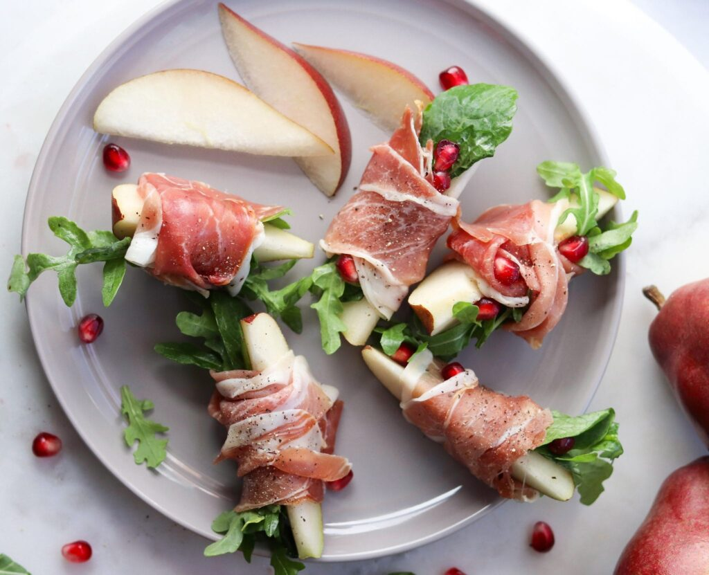 prosciutto wrapped pears on a white plate