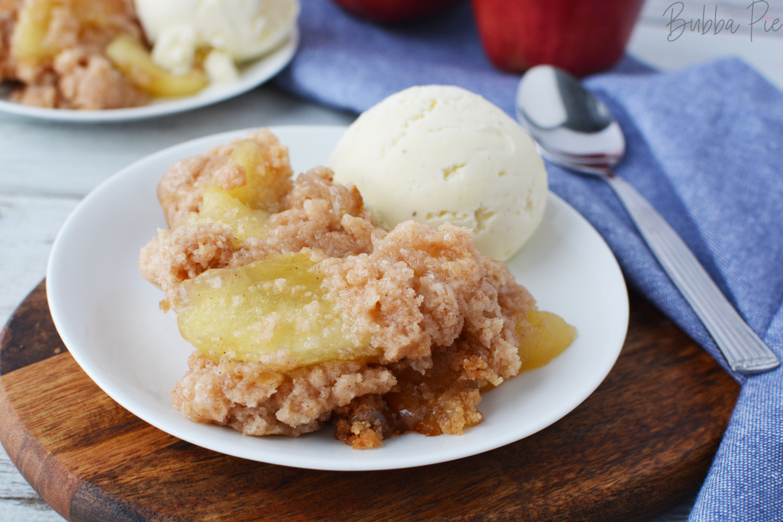 Crockpot Apple Dump Cake served warm on a plate with vanilla ice cream