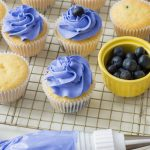 Lemon Blueberry Cupcakes getting topped with buttercream frosting