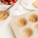 scoop graham cracker mixture in tin to make crust.