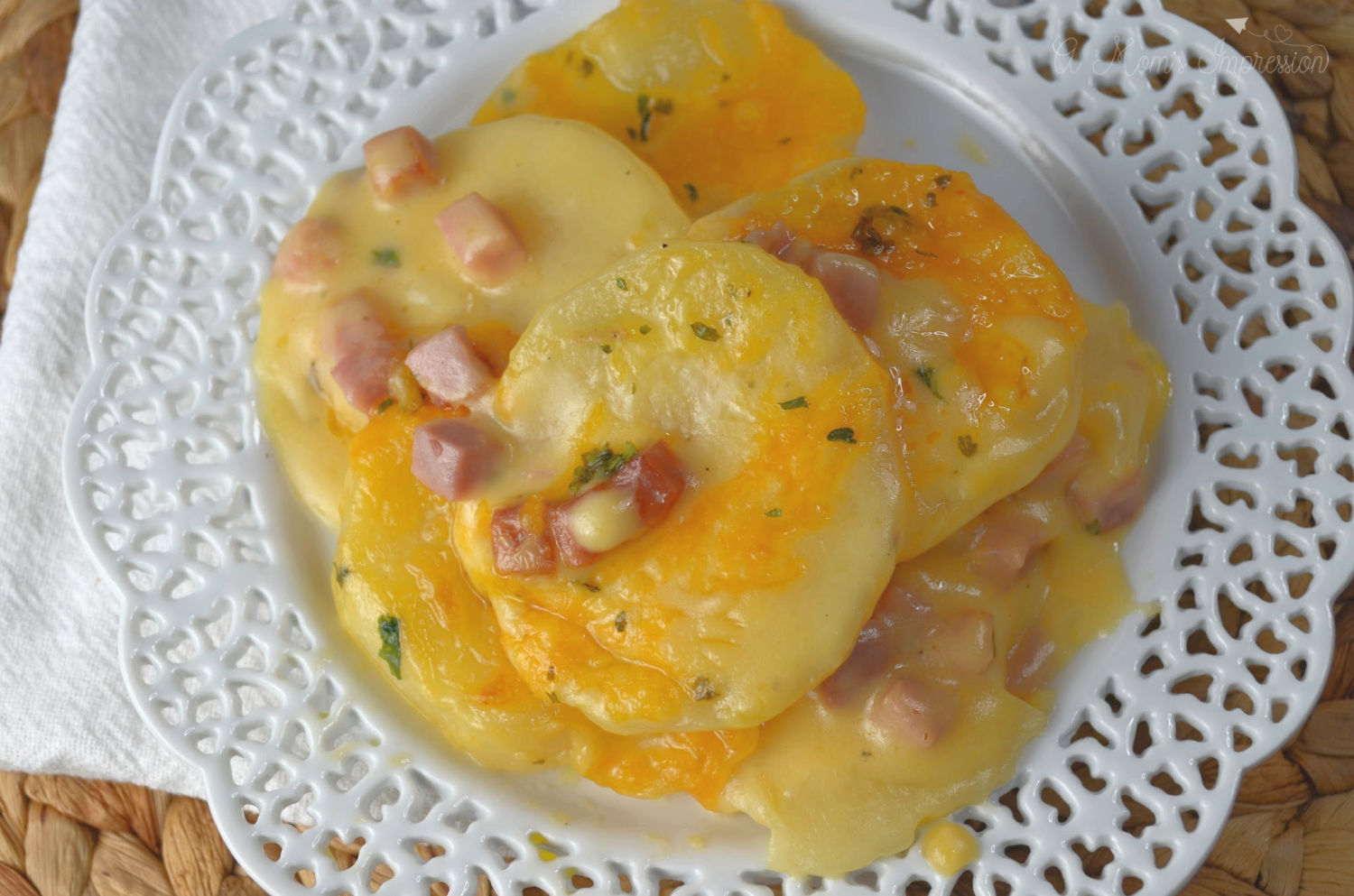 Scalloped potatoes with ham on a white serving dish