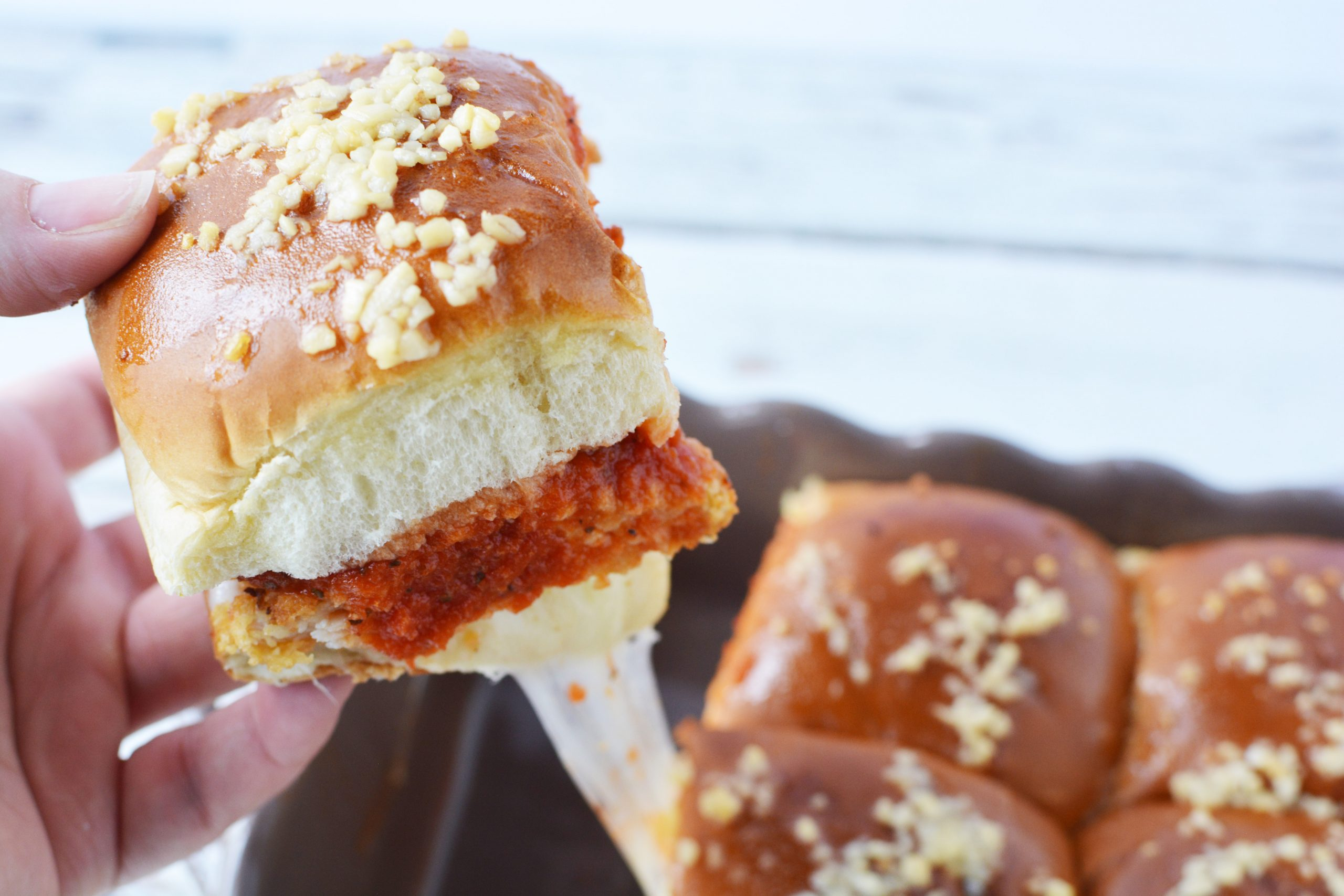 Chicken Parmesan Sliders Recipe has breaded chicken, marinara sauce and provolone cheese on a hawaiian roll.