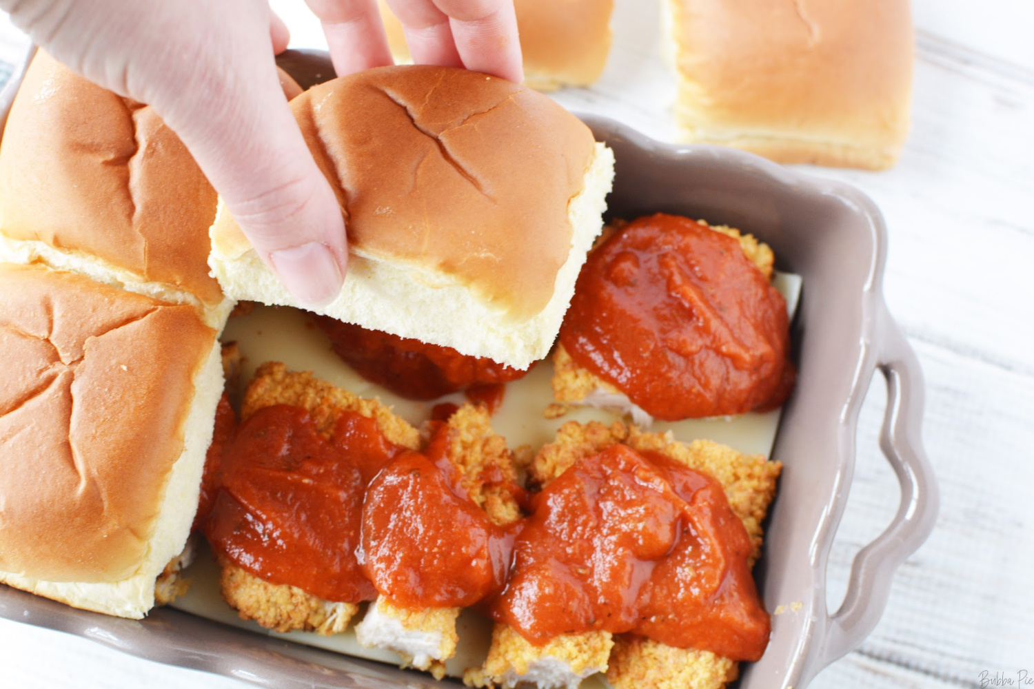 Easy Chicken Parmesan Sliders are covered with provolone cheese and marinara sauce before going on the oven.