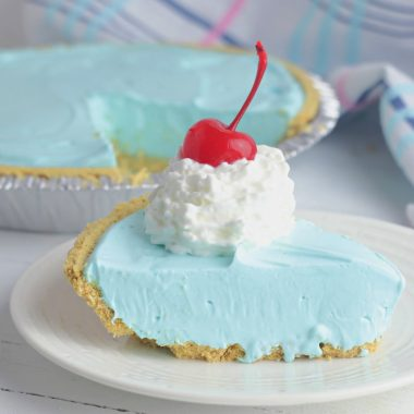 Kool Aid Pie topped with whipped cream and a cherry.