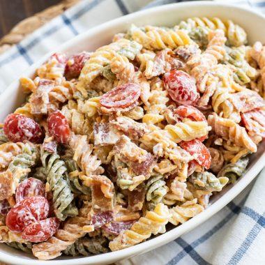 Bacon Ranch Pasta Salad has sour cream, mayonnaise, cheese and tomatoes.