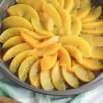 peach Upside Down Cake Instructions include putting the sliced peaches on a layer of cinnamon and brown sugar and butter.