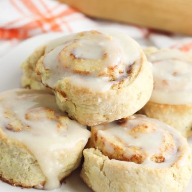 Pumpkin Cinnamon Rolls with a cream cheese glaze on a serving plate.