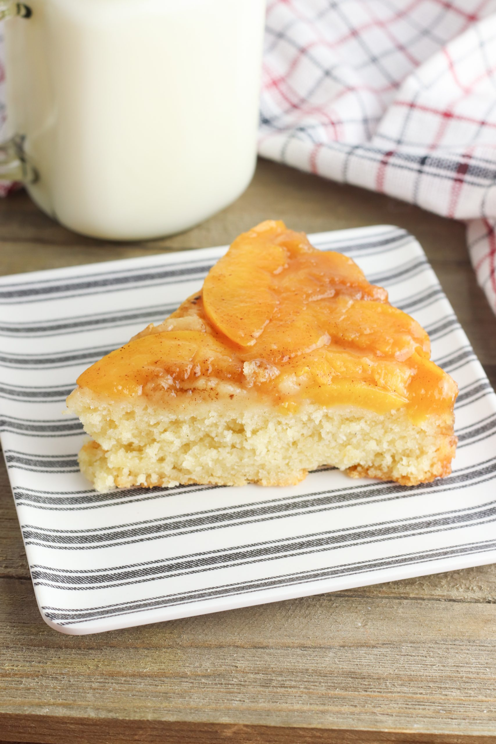 Upside Down Peach Cake Recipe being served for dessert on a plate with milk.
