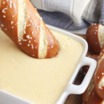 Dipping a soft pretzel in Beer Cheese Dip.