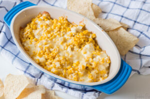 Hot Corn Dip being served in a bowl as an appetizer at a party.
