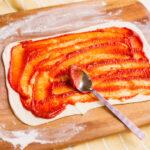 Spread tomato sauce on pinwheel pastry