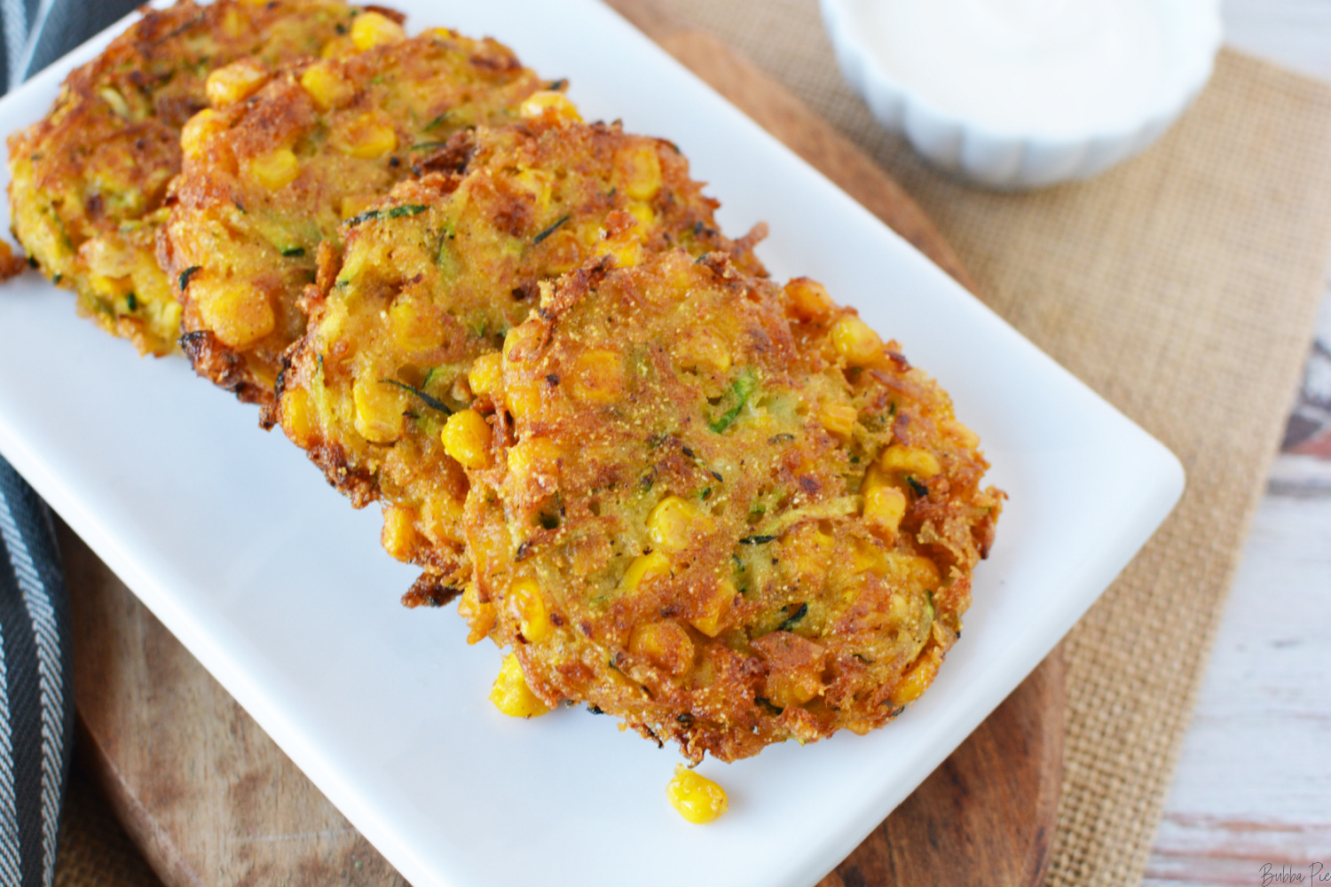 Zucchini Corn Fritters being served on a white plate.