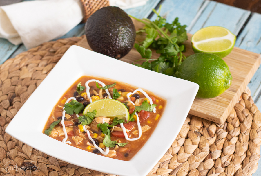 Easy Taco Soup being served in a bowl with lime and avocado.