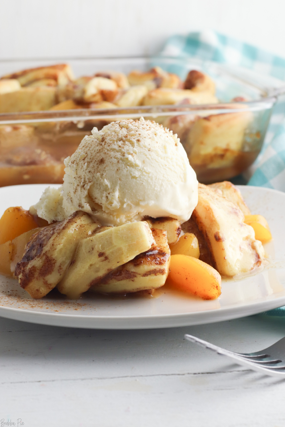 Cinnamon Roll Peach Cobbler Recipe being served on a white plate.