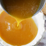 Pouring Honey Pie Mixture into pie crust.