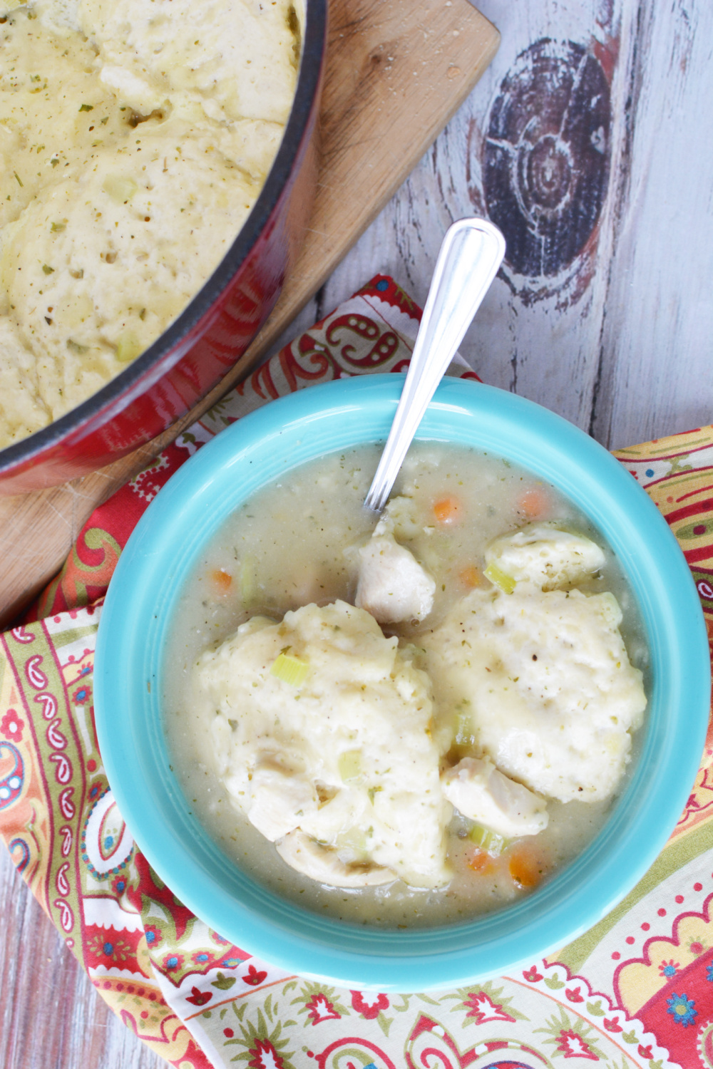 Easy Bisquick Chicken and Dumplings in a blue bowl with a spoon.