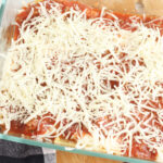 layering lasagna with cheese, sauce and noodles