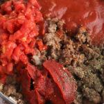 Add tomato sauce to rigatoni arrabbiata