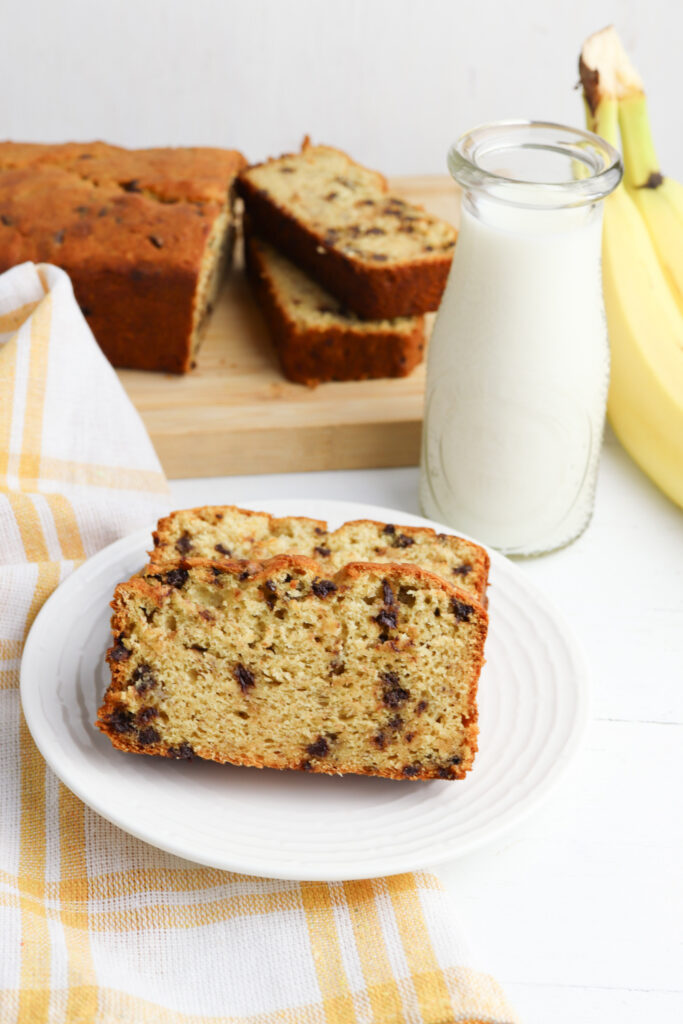 banana bread on a white plate with milk.