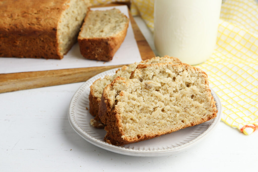 banana bread on a white plate with a glass of milk.