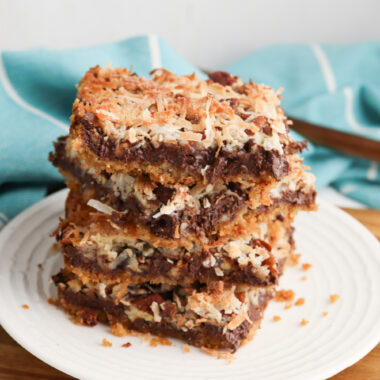 Hello Dolly Bars stacked on a white plate.